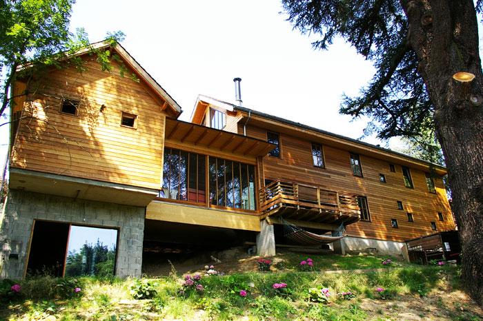 Façade sud avec de nombreuses fenêtres d'une grande maison en bois